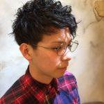 メガネをかけたショートパーマの男性の写真